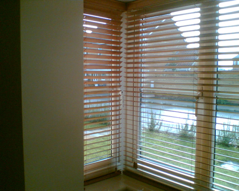 bay beige and black in stock blinds on cream fireplace living room with photo shelf unit sofas beside window television