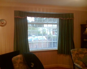 Venetian blind in bay window with curtains open