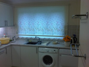 Roller blind with border pattern fitted over kitchen sink from Baileys Blinds.
